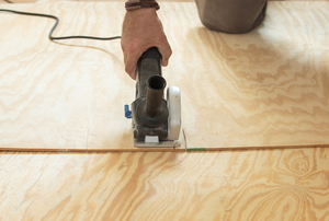 A circular saw cutting plywood subflooring.