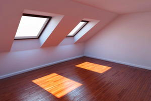 Windows projecting squares of light onto a wood-paneled in a finished attic.