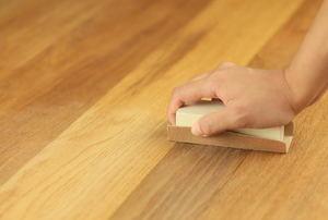 Someone sands hardwood floors.