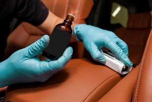 hands with essential oil bottle cleaning car upholstery