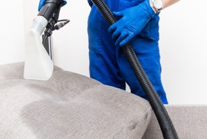 a person with gloves cleaning a couch cushion with a vacuum cleaner