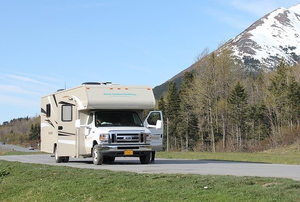 an RV on the road with mountains in the background