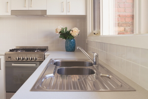 A stainless steel kitchen sink in a pristine kitchen.