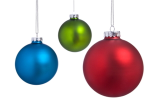 Three Christmas ornaments hanging in front of a white background.