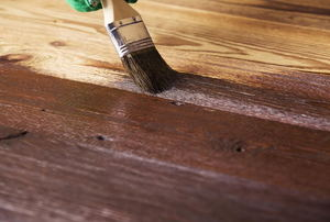 A dark wood flooring stain being applied with a paint brush.