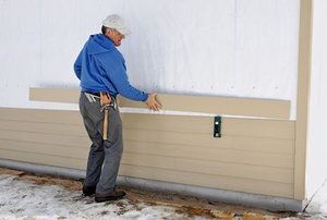 Carpenter installing siding