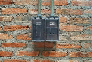 electrical boxes mounted to a brick wall
