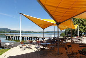 shade sails on a patio near water