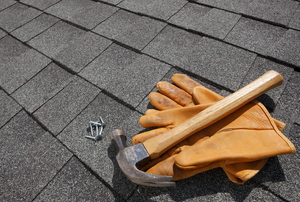 Gloves, a hammer, and roofing nails sit on a shingled roof.