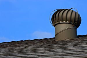 A turbine vent on a roof against a blue sky.