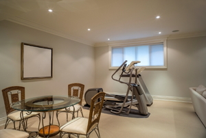 a basement with a table and chairs and a treadmill