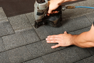 A roofing expert uses a nail gun to secure new shingles to the roof.