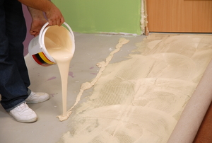 Carpet glue being poured onto concrete flooring in preparation for installing carpet.