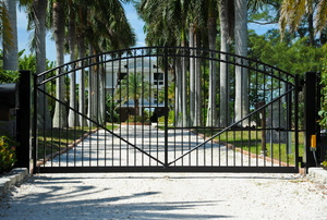 A sliding electric gate in a driveway in front of a large home with palm trees.