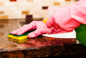 gloved hands washing a countertop with a sponge