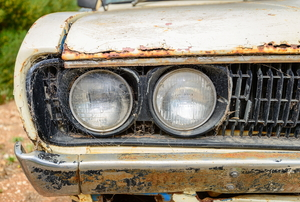 An old car with rust deposits on the chrome bumper.