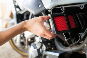 hand replacing air filter on motorcycle