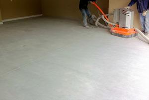 A plain concrete floor inside of a garage.
