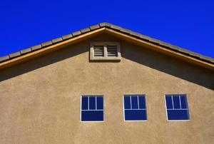 A gable vent and three windows on a stucco house.