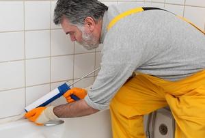 man caulking bathtub