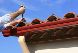 A man installs rain gutters.