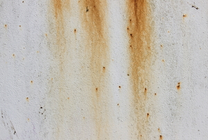 Rust stains on a painted metal plate.