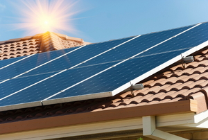 A set of solar panels on a red tile roof with a sun shining over it.