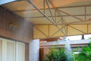 Misters on an awning above a patio.