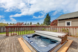 A hot tub with an attached cover sitting on a deck.