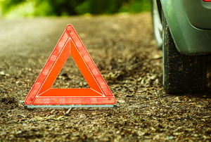 An emergency triangle next to a car tire.