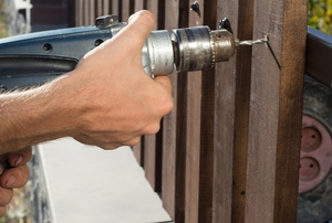 hands drilling metal panels onto fence