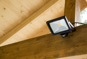 An outdoor flood light on a wooden wall.
