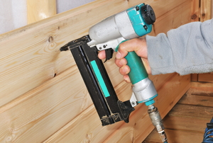 A nail gun being used to nail wood boards to supports.