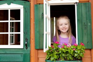 young girl looking out of playhouse window