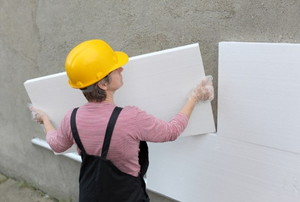 Worker installing foam board onto a cement wall