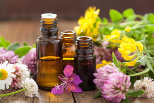 A trio of essential oils surrounded by flowers.