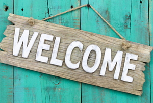 "A decorative wooden sign that reads ""welcome""."
