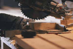 A man cutting wood with an electric circular saw