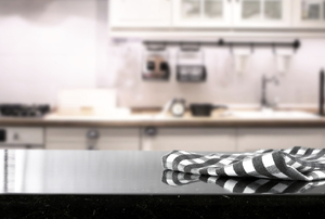 A black countertop with a checkered towel on it.