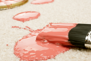 pink paint spilled on a carpet floor with a brush
