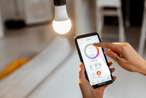 hand using phone to control smart light