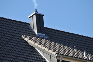 smoke drifting out of a chimney on a roof