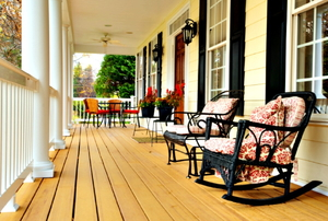 A classic front porch with a rocking chair and several other chairs for seating.