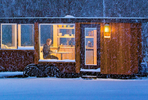 man working on computer in mobile home in a snowy forest