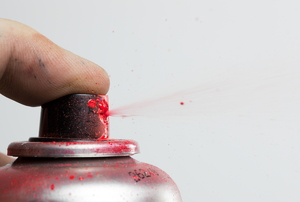 A finger holding down the nozzle of a bottle with red spray paint.