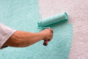 A homeowner painting a teal color over a stuccoed surface.