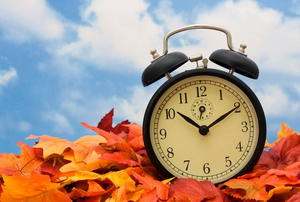 An alarm clock sitting in a pile of autumn leaves.