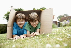 A couple of boys playing in a large cardboard box.