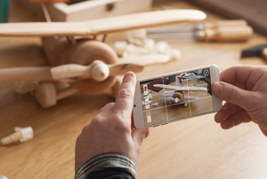 hands holding a phone taking a picture of a wooden airplane toy