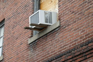 Side of a brick building with a window AC unit installed in a window